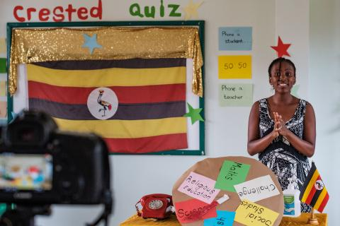 Education in Uganda: A teacher in front of a camera hosting a TV show in a school classroom.