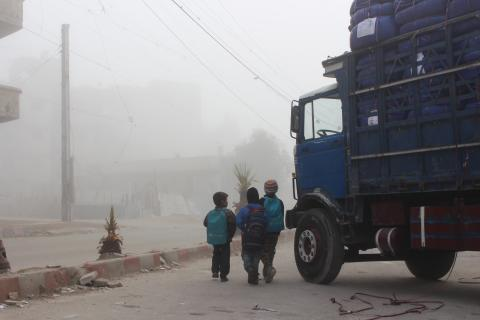 Children in backpacks stand next to a truck