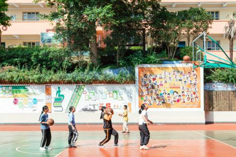 China. Children play basketball in a playground.