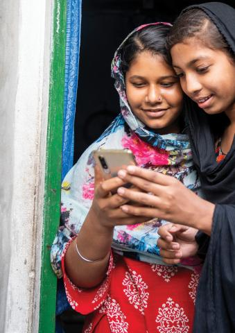 Two young girls looking at a mobil cellphone