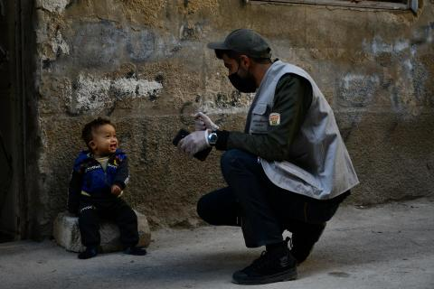 Syria. A man speaks with a child sitting on a doorstep.