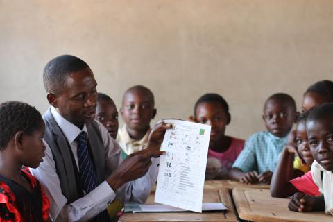 Data for better quality education: a volunteer shows school profile cards to students in a classroom.