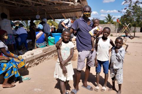 Mozambique. A family stands outside a shelter.