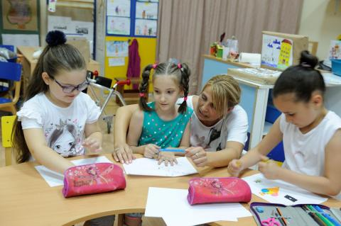 A girl with cerebral palsy in a kindergarten in Serbia with her teacher and two other students