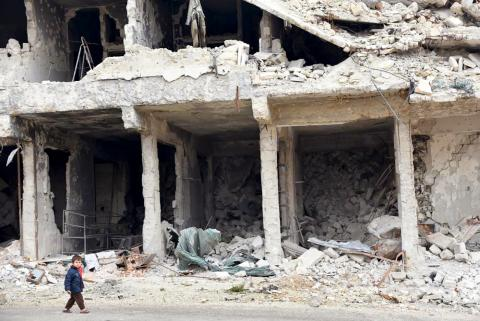 A child walks past a destroyed building in Aleppo, Syria.