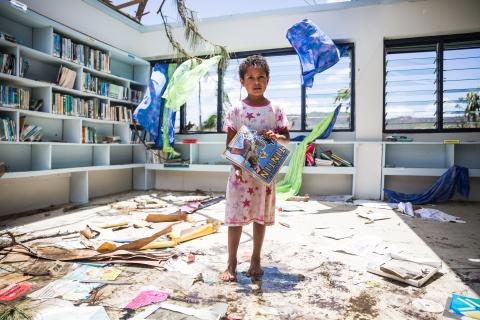 Makelesi, 7, standing in destroyed library of Nabau District School in Ra Province in Fiji.