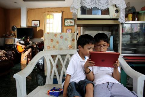 Two brothers look at an iPad in the Central Visayas city of Cebu, Philippines.