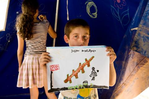 A boy displaying his drawing in an art class in a tent serving as a 'child-friendly' space in Georgia.