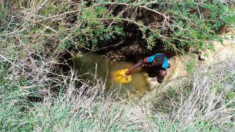 A girl fetches water from a puddle, Madagascar