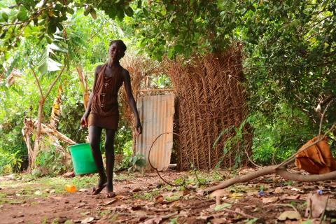 Guinea-Bissau: a girl carries a bucket of water.