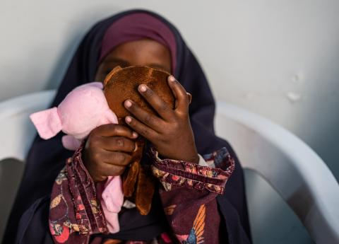 A young girl plays with toys as she waits to begin her counselling session at Somali Women's Development Center (SWDC) in Mogadishu, Somalia.