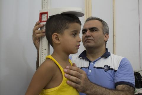 A man measures a child's height, Syrian Arab Republic