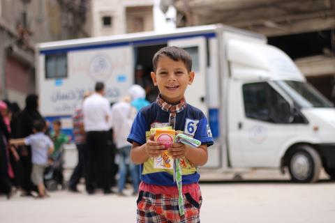 A boy stands in front of a mobile health clinic, Syrian Arab Republic
