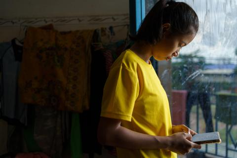 In Cambodia, Nha Nha follows an online lesson streamed via Facebook on a tablet at home.