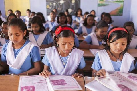 Students in India sit at their desks.