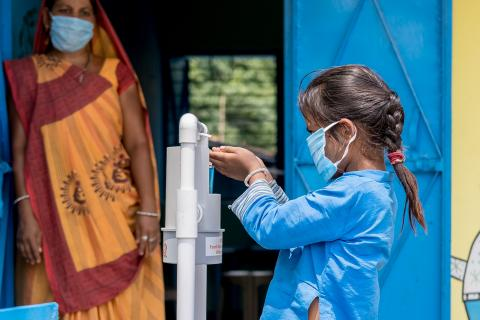Payal Patel, six years old, uses a foot pedal sanitizer installed outside the AW before entering. Anganwadi workers (AWW) guiding children to use sanitizers and the correct way of wearing masks.