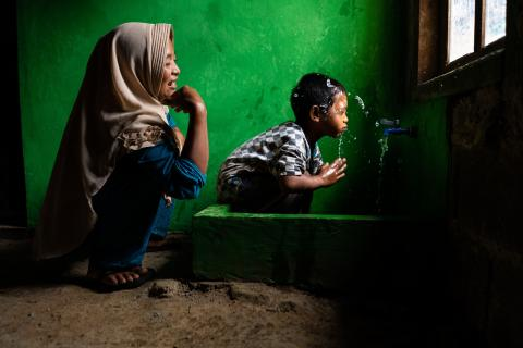 Mother and sonin a newly built clean water and sanitation facility in their home in Tlogopakis village, Indonesia.