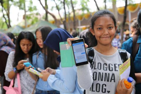 Indonesia. A girl holds up her cell phone.