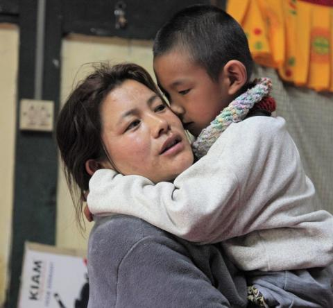 Bhutan. A mother holds her son.