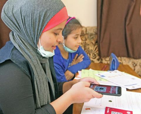 School girls in Jordan scanning a QR Code to access online educational resources
