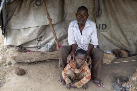 Mozambique. A man and child sit outside a tent.