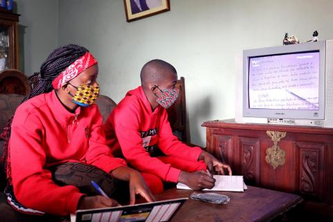 Mozambique. Two teenagers watch an education programme on TV.