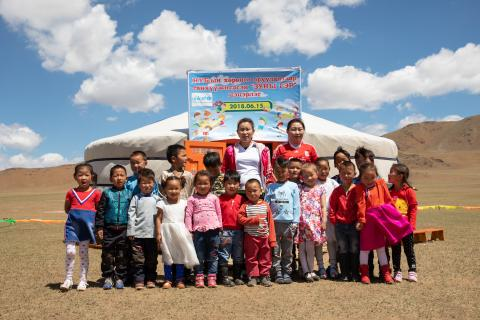 Young children and teachers, from a nomadic herder community, outside a newly opened mobile 'ger' (traditional nomadic tent) kindergarten, in Bayankhongor Province, Mongolia.