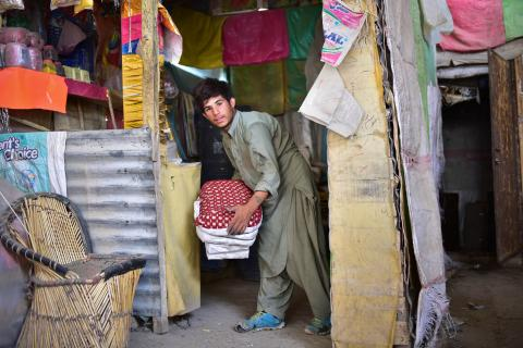A boy lifts a crate at a market, Pakistan