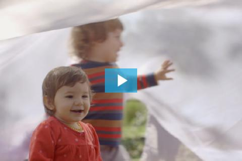 Two children play under a sheet