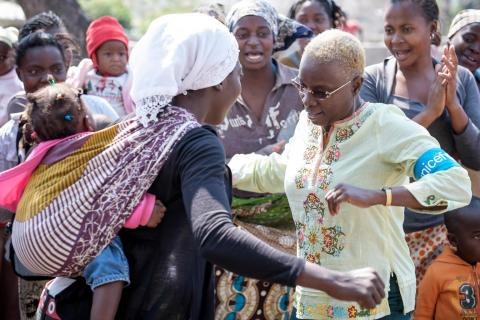 UNICEF Goodwill Ambassador Angelique Kidjo dances with a woman carrying a baby in a sling pouch on her back, during a nutrition education session for mothers in the Madinguine community in Moamba.