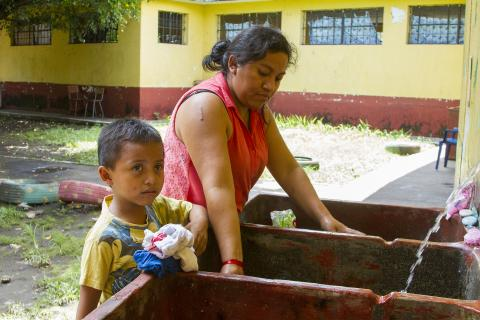 A woman washes clothes with her son, Guatemala