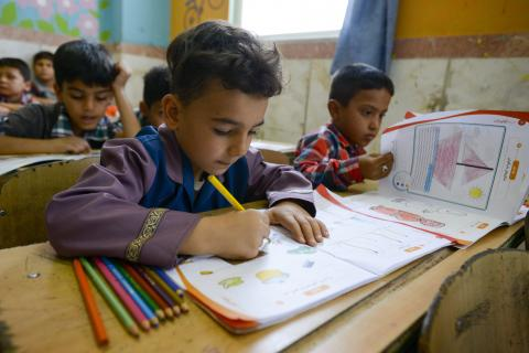 Refugee children study in a classroom.