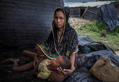 A woman holds her child in her lap, Bangladesh
