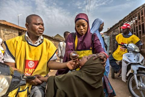 On a street in Nigeria, two health workers provide an oral polio vaccine to a child.
