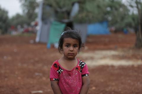Syria. A girl stands near a makeshift camp near the border with Turkey.