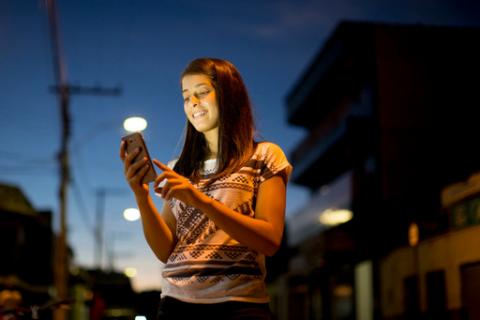 A girl checks her mobile phone on a street in Taiobeiras municipality in the Southeastern state of Minas Gerais, Brazil.