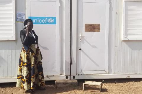 South Sudan. A woman talks outside on a cell phone.