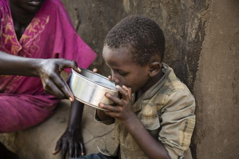 A mother gives water to her son to drink in South Sudan.
