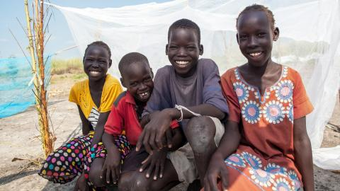 Friends sit by a UNICEF-supplied mosquito net in Bienythiang in Akoka county, Upper Nile state, South Sudan.