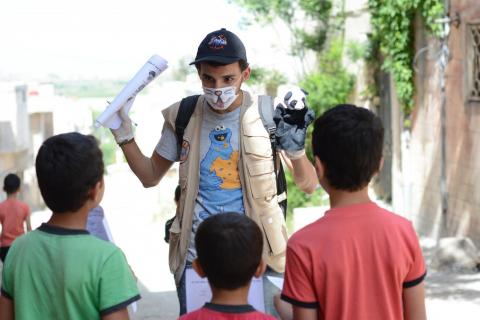 Syria. A volunteer talks with children.