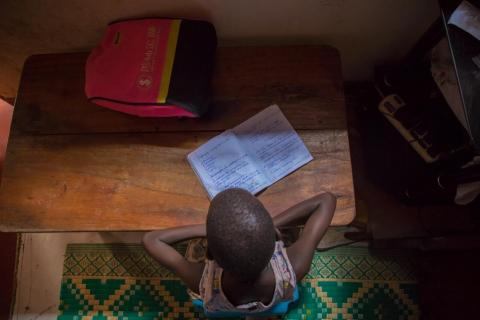 Uganda. A child studies at home.