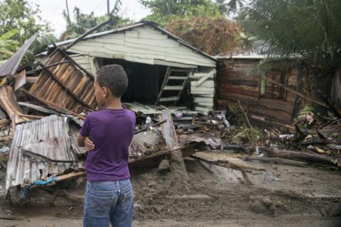 Dominican Republic. A child stands in front of a destroyed home.