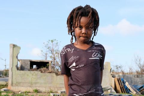 Anguilla. A girl stands near a partially destroyed brick building.