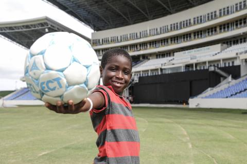 A boy holds a football, Antigua