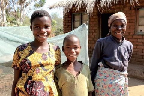 Meria Maulana and her grandchildren Estere and Francis stand cheerfully outside their home in Balaka, Malawi.