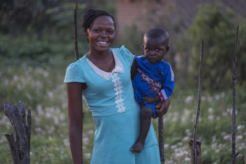 An adolescent girl smiles as she carries a young boy on her hip.