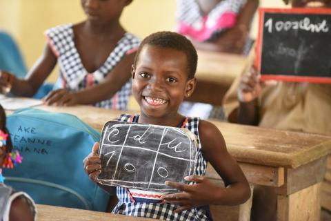 A smiling young student holds a small chalkboard in a classroom in Côte d'Ivoire.