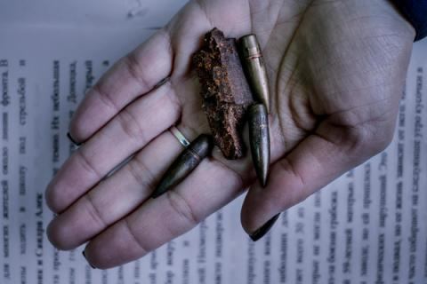 A school director holds a shell fragment and bullets in eastern Ukraine