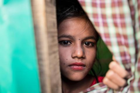Rohingya refugee Saleha, 10, looks out of her family's shelter in Kutupalong makeshift settlement, Cox's Bazar District, Bangladesh.