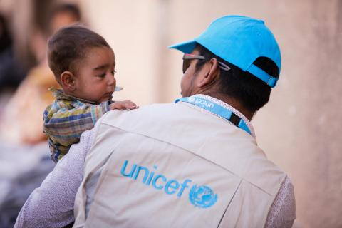 A man in a UNICEF jacket holds a baby, Syrian Arab Republic